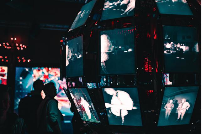 people looking at multiple video screens