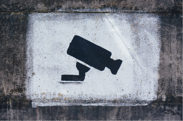 security camera spray painted on wall